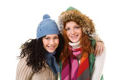 two friends in warm knitted clothes looking at camera over white background - stock photo