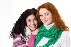 Portrait of pretty girls wearing sweaters and scarves and looking at camera with Stock Photos