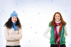 Two friends in warm knitted clothes looking at camera over snowflake background Stock Photos