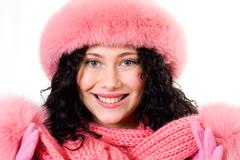 Face of pretty woman wearing pink winter fur cap over white background Stock Photos