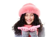 cheerful woman in pink winter fur cap looking at her palms with smile - stock photo