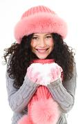 portrait of cheerful woman in pink winter fur cap holding snow in hands - stock photo