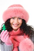 cheerful woman wearing pink winter fur cap showing toy firtree in her hand - stock photo