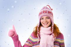 image of cool girl showing thumb up over snowflake background - stock photo