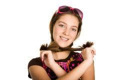 Portrait of cute girl crossing her pony tails by neck looking at camera with smi Stock Photos