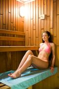 Peaceful woman taking pleasure in hot sauna while sitting on blue towel on woode Stock Photos