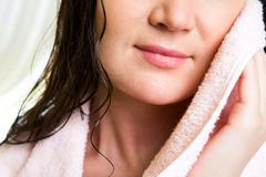 Lower part of female face drying herself with soft towel Stock Photos