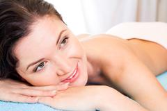 Beautiful and happy woman waiting for massage in spa salon Stock Photos