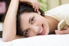 pretty young female relaxing on bed and looking at camera - stock photo