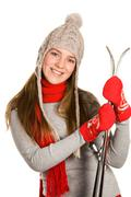 portrait of positive sporty woman with skis looking at camera and smiling - stock photo