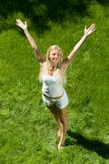 above view of happy girl standing on green grass with stretched arms - stock photo
