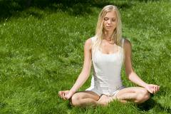 Image of meditating girl seated in pose of lotus on green grass Stock Photos