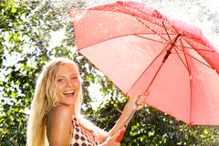 Portrait of happy girl with red umbrella looking at camera in park Stock Photos