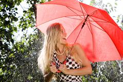 portrait of happy girl laughing under red umbrella - stock photo