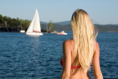 rear view of beautiful blonde on background of blue ocean - stock photo