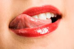 Close-up of female licking her lips by tip of the tongue after eating something Stock Photos