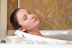Image of relaxing woman with closed eyes having pleasant bath with seashells nea Stock Photos
