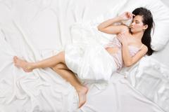 above view of pretty female in peignoir sleeping on bed under silk sheets - stock photo