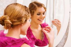 Image of pretty female with earring in hand during christmas preparations Stock Photos