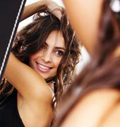Image of pretty female looking in mirror and enjoying herself Stock Photos