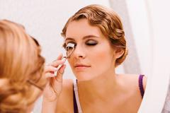 Image of pretty female looking in mirror while curling her eyelashes Stock Photos