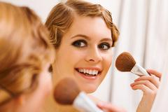 image of pretty female looking in mirror and doing makeup - stock photo