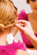 Image of pretty female putting on earrings Stock Photos