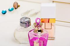 Image of three bottles of scents on lady toiletries table Stock Photos