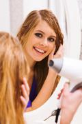 image of pretty female looking in mirror while drying her hair - stock photo