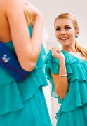 Stock Photo of image of pretty female in green dress looking in mirror with smile