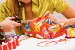 Close-up of female hands wrapping christmas presents Stock Photos