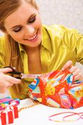 Happy woman wrapping christmas presents before holiday Stock Photos