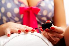 Close-up of female polishing her nails with red lacquer Stock Photos