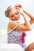 Portrait of female in curlers touching her head and speaking on the telephone at Stock Photos