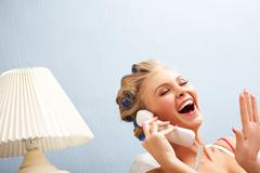portrait of female in curlers laughing while speaking on the telephone - stock photo