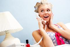 portrait of surprised female in curlers speaking on the telephone at home - stock photo
