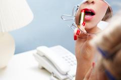 Close-up of female applying red lipstick while looking into mirror Stock Photos