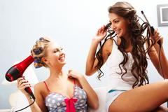 photo of joyful females taking care of their hair while chatting - stock photo