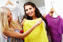 image of pretty females looking at smart dress while choosing a right one - stock photo