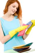 Portrait of young female holding plate and washing it Stock Photos