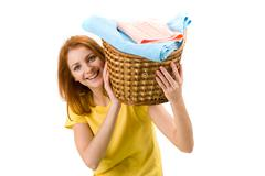 Portrait of young female holding basket full of colorful towels Stock Photos