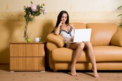 image of pretty girl looking at laptop monitor while sitting on leather sofa - stock photo