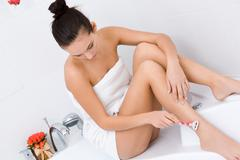 Photo of beautiful young woman making depilation of leg skin Stock Photos