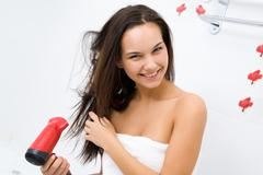 Photo of joyful female drying her hair after washing it Stock Photos