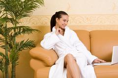 Image of pretty girl in bathrobe looking at laptop monitor while sitting on leat Stock Photos