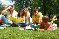 portrait of cheerful friends talking and reading in park together - stock photo