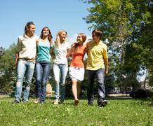 Photo of cheerful friends walking down green grass in park and chatting Stock Photos