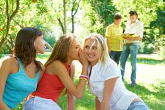 Photo of three girls whispering with each other about guys on background Stock Photos