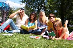 Portrait of smart friends reading books in park together Stock Photos