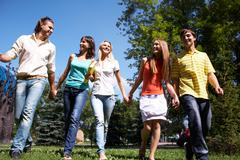 photo of several happy friends walking in park and chatting - stock photo